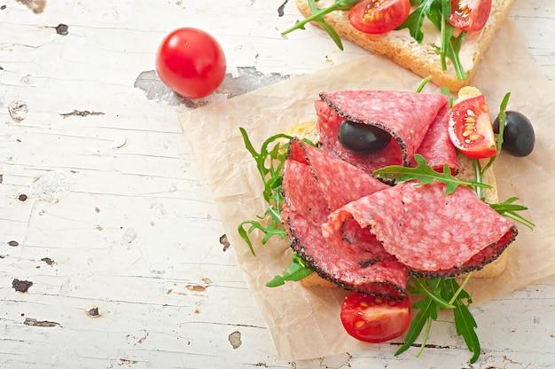Kanapka z kiełbasą, oliwką, pomidorem i rukolą