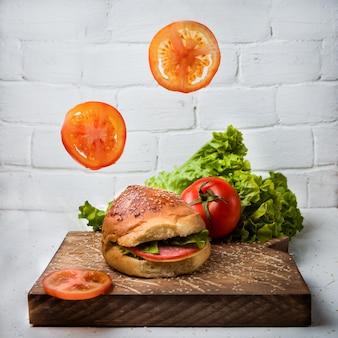Kanapka z kiełbasą z pomidorem i sałatą w drewnianej desce