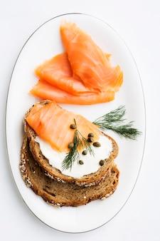 Kanapka z kremem serowym i wędzonym łososiem udekorowana koprem włoskim