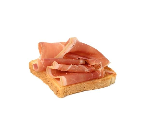 Kanapka z kromką białego chleba i prosciutto na białym tle