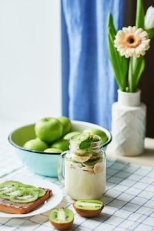 Kanapka z masłem orzechowym i kiwi, zielonymi jabłkami, jogurtem z bananem i kiwi, ciekawy pomysł na śniadanie dla dzieci, deser lub posiłek świąteczny, widok z góry leżał płasko, zdrowe jedzenie dla dzieci. dzień dobry