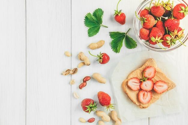 Kanapka z masłem orzechowym ze świeżą truskawką na białym tle. zdrowe letnie śniadanie lub przekąska.