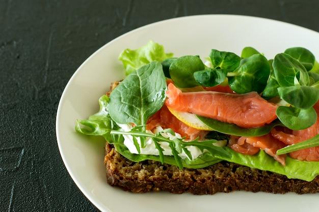 Kanapka z miękkim serem wędzonym łososiem, kratą i cytryną. pomysł na smaczny i zdrowy posiłek.