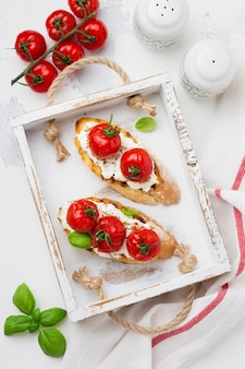 Kanapka z pieczonymi pomidorkami cherry, czosnkiem, oliwą i twarogiem na białej powierzchni