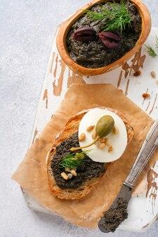 Kanapka z plasterkiem sera mozzarella i tapenada, kapar na jasnoszarym tle rustykalnym tabeli. tradycyjne danie prowansalskie. selektywne skupienie