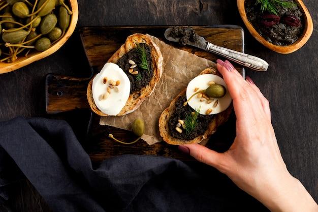 Kanapka z plasterkiem sera mozzarella i tapenadą, kaparami na tle ciemnego stołu rustykalnego. ręka trzyma kanapkę. tradycyjne danie prowansalskie. widok z góry