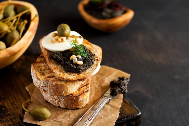 Kanapka z plasterkiem sera mozzarella i tapenadą, kaparami na tle ciemnego stołu rustykalnego. tradycyjne danie prowansalskie. selektywne skupienie