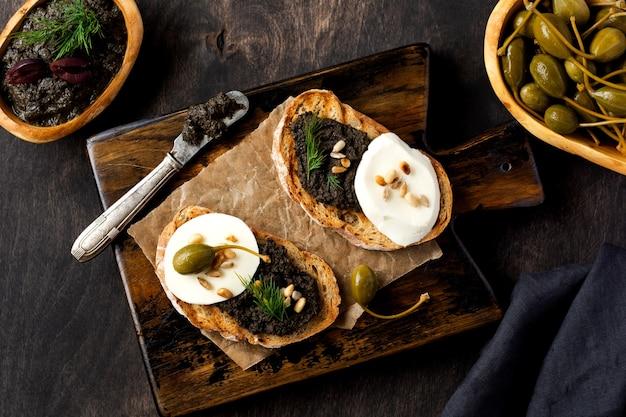Kanapka z plasterkiem sera mozzarella i tapenadą, kaparami na tle ciemnego stołu rustykalnego. tradycyjne danie prowansalskie. widok z góry
