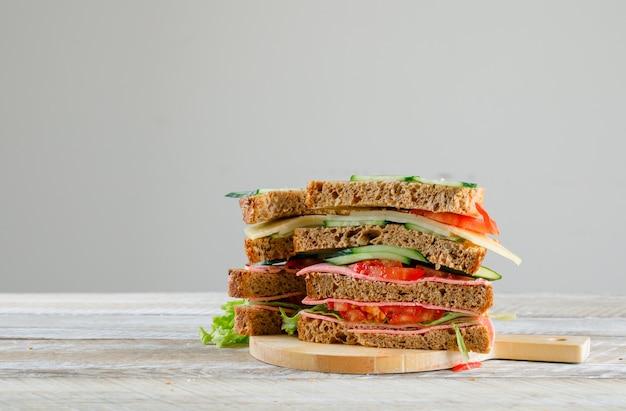 Kanapka z pomidorem, ogórkiem, serem, kiełbasą, ziołami na desce do krojenia na stole drewnianym i szarym, widok z boku.