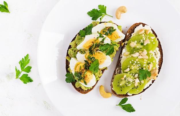 Kanapka z puree z awokado, jajkiem na twardo i serkiem kanapkowym, kiwi, orzechami