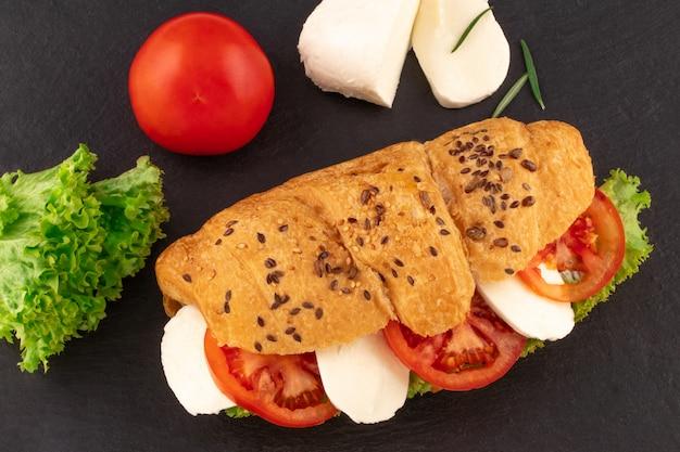 Kanapka z rogalika z mozzarellą sałaty i pomidorem na czarnym kamieniu.