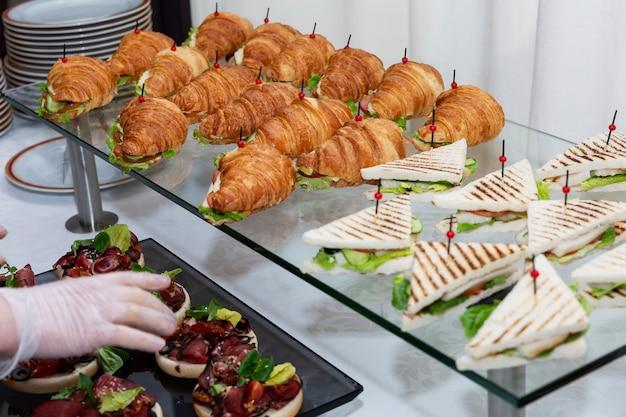 Kanapka z rogalikiem na stole w formie bufetu. catering na spotkania biznesowe, imprezy i uroczystości.