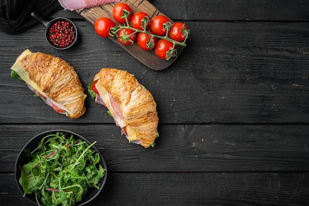 Kanapka z rogalikiem z prosciutto, pomidorami, zestawem serów, ziołami i składnikami, na tle czarnego drewnianego stołu, widok z góry na płasko, z miejscem na tekst