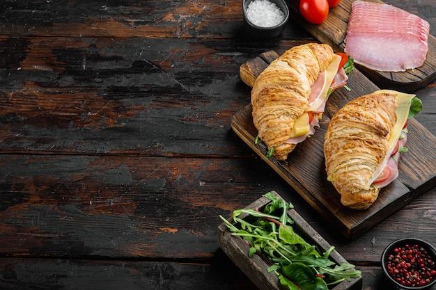 Kanapka z rogalikiem z prosciutto, pomidorami, zestawem serów, ziołami i składnikami, na tle starego ciemnego drewnianego stołu, z miejscem na tekst