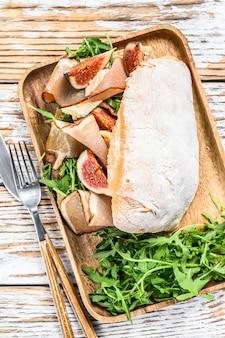 Kanapka z rukolą, figą, prosciutto, ciabattą i serem pleśniowym na drewnianej tacy. białe tło. widok z góry.