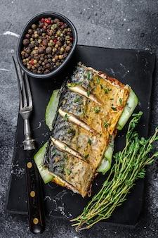 Kanapka z rybą makreli, ogórkiem i musztardą. czarne tło. widok z góry.