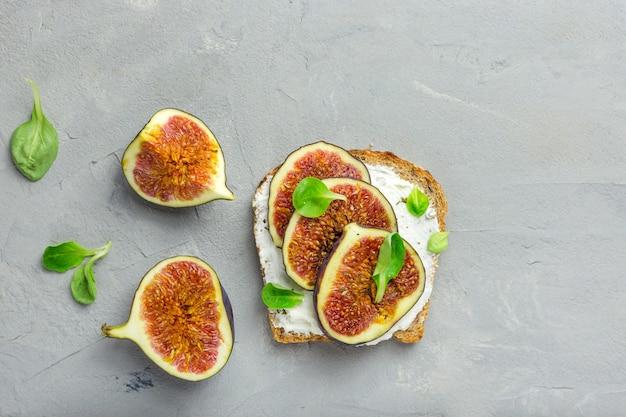 Kanapka z serem, figami, sałatką z miodu i liści na drewnianej desce rustykalnej na szaro