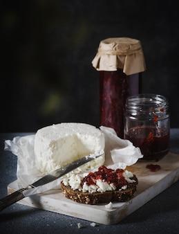 Kanapka z serem i dżemem na desce do krojenia