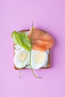 Kanapka z serem mascarpone, jajkami, łososiem na różowej ścianie. widok z góry.