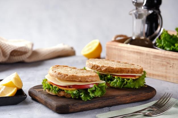 Kanapka z serem, pomidorem i świeżą sałatką, z pieczywa pełnoziarnistego z chrupiącą skórką na zbliżeniu drewnianej deski
