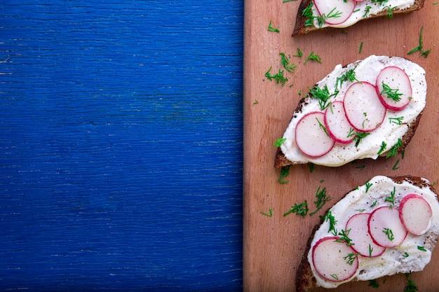 Kanapka z serem rzodkiewnym na pokładzie na niebieskim drewnianym. widok z góry. copyspace.