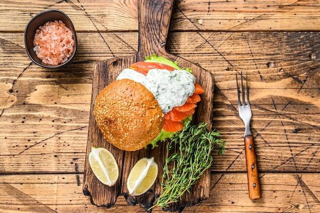 Kanapka z solonym łososiem rybnym, awokado, bułką burgerową, sosem musztardowym i sałatką lodową. drewniany stół. widok z góry.