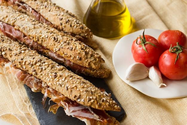 Kanapka z szynką hiszpańską z oliwą z oliwek, pomidorem i czosnkiem. tradycyjna przystawka kuchni katalońskiej znana jako bocadillo de jamón, przygotowywana z szynki iberyjskiej, na rustykalnym tle