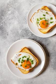 Kanapka z szynką, serem i jajkiem. tradycyjna francuska kanapka croque-madame podana na białym talerzu. popularny francuski posiłek w kawiarni. szare tło. widok z góry. miejsce na tekst