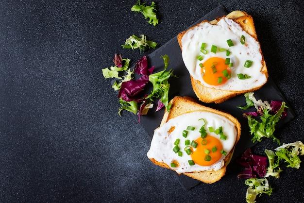 Kanapka z szynką, serem i jajkiem. tradycyjna francuska kanapka croque-madame podawana z liśćmi sałaty na czarnym talerzu. popularny francuski posiłek w kawiarni. czarne tło. widok z góry. miejsce na tekst