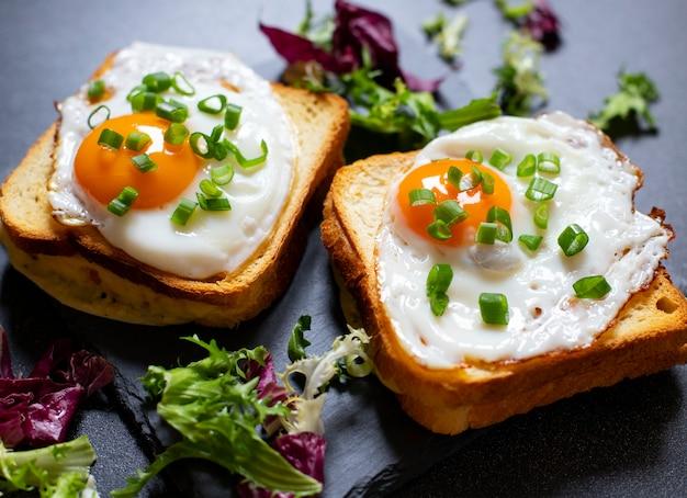 Kanapka z szynką, serem i jajkiem. tradycyjna francuska kanapka croque-madame podawana z liśćmi sałaty na czarnym talerzu. popularny francuski posiłek w kawiarni. czarne tło. zbliżenie