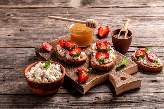 Kanapka z truskawkami, miękkim serem ricotta i miętą, miodem, chia na podłoże drewniane