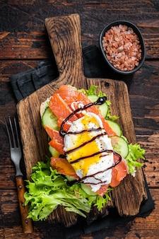Kanapka z wędzonym łososiem z jajkiem po benedyktyńsku i awokado na chlebie. ciemne drewniane tło. widok z góry.
