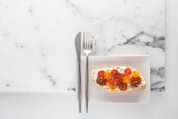 Kanapka z widokiem z góry z twarogiem i pomidorami na talerzu ze sztućcami