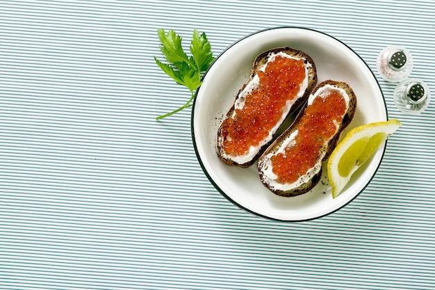 Kanapka ze świeżego chleba z czerwonym kawiorem i serem miękkim na talerzu. klasyczne połączenie składników.
