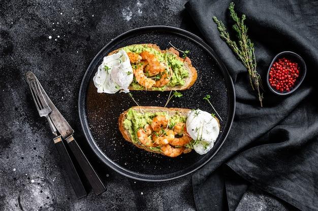 Kanapka zwieńczona świeżymi krewetkami, krewetki na awokado z jajkiem. zdrowe jedzenie, kuchnia skandynawska. czarne tło. widok z góry