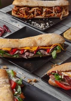 Kanapki bagietkowe z różnymi składnikami podawane na ceramicznych talerzach na drewnianym stole. obraz na białym tle. różnorodne kanapki