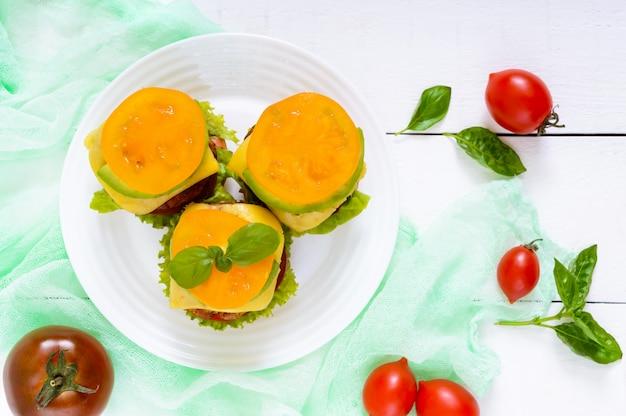 Kanapki (burgery) z żółtymi i czarnymi pomidorami, soczystym kotletem, awokado na talerzu na białym drewnianym.
