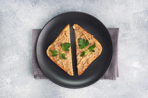 Kanapki chrupiące tosty i pasztet z wątróbki drobiowej z natką pietruszki na czarnym talerzu. na szarym betonowym stole. skopiuj miejsce.