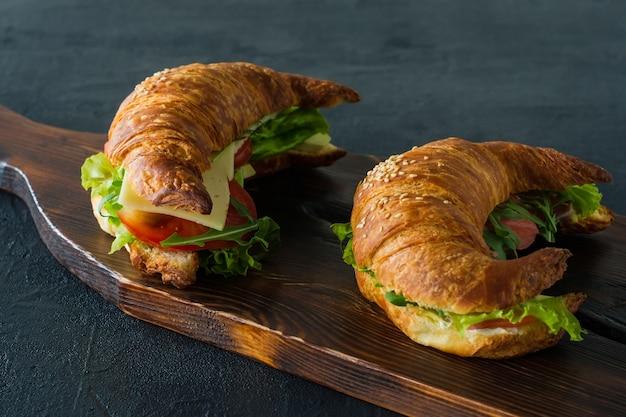 Kanapki croissant z solonym łososiem na biurku, podawane ze świeżymi liśćmi sałaty,