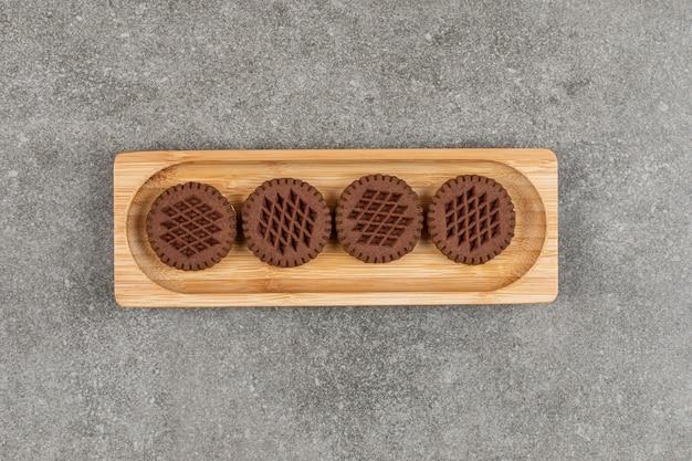 Kanapki czekoladowe ciasteczka na drewnianym talerzu.