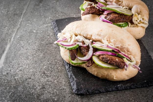 Kanapki fast food. tradycyjne chińskie azjatyckie bułeczki bao z farszem mięsnym wieprzowiną, wołowiną, świeżymi warzywami i ostrym sosem. na ciemnym kamiennym stole.