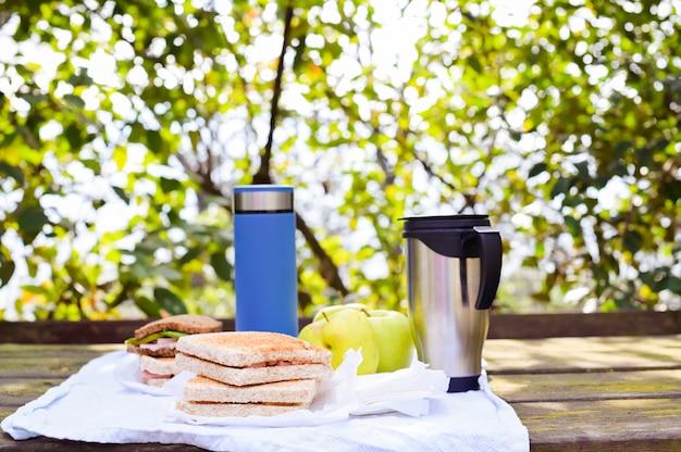 Kanapki i dwa termosy z herbatą i kawą na drewnianym stole w parku na tle zieleni liście, drzewo i światło słoneczne. pojęcie turystyki i podróży. skopiuj miejsce