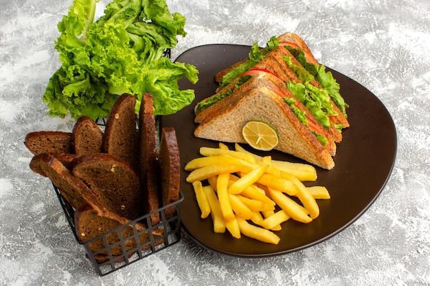 Kanapki i frytki wraz z zieloną sałatą i czarnym pieczywem na szaro