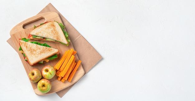 Kanapki, jabłka i marchewki na desce na torbie kraft na szarym tle. przygotowanie obiadu szkolnego. widok z góry, kopia przestrzeń.