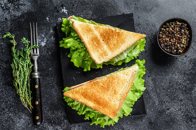 Kanapki klubowe z szynką wieprzową, serem, pomidorami i sałatą na drewnianej desce do krojenia. czarne tło. widok z góry.
