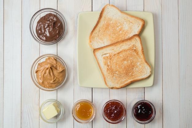 Kanapki lub grzanki z masłem orzechowym, pastą czekoladową i galaretką truskawkową, porzeczkową i morelową lub dżemem na białym drewnianym stole, widok z góry, układ płaski