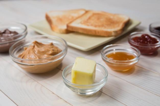 Kanapki lub tosty z masłem orzechowym, pastą czekoladową i galaretką truskawkową, porzeczkową i morelową lub dżemem na białym drewnianym stole, z bliska