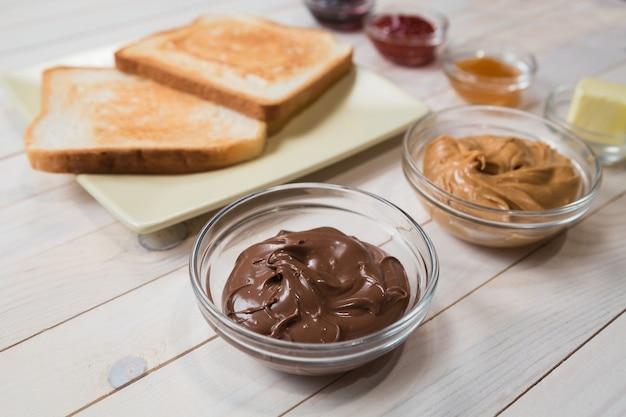 Kanapki lub tosty z masłem orzechowym, pastą czekoladową i galaretką truskawkową, porzeczkowo-morelową lub dżemem na białym drewnianym stole