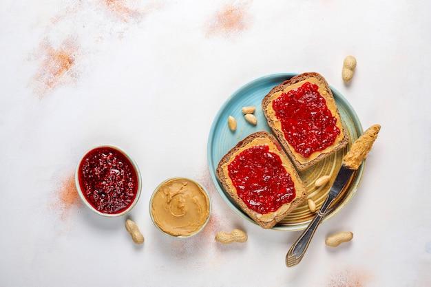 Kanapki lub tosty z masłem orzechowym z konfiturą malinową.