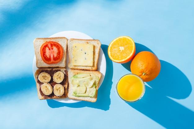 Kanapki na białym talerzu, szklance soku pomarańczowego w pomarańczach, niebieskiej powierzchni. leżał płasko, widok z góry.